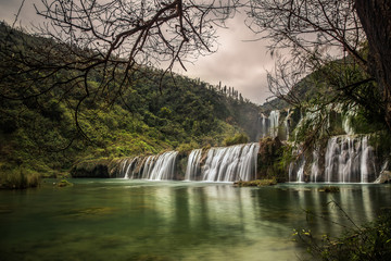 Waterfall in forest with cloudy sky