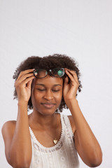 Woman smiling and arranging glasses on her head