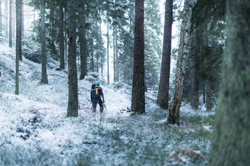 Man walking through winter forest