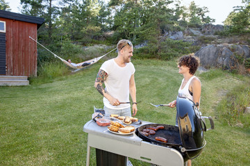 Couple preparing food on barbecue