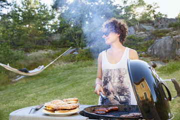 Woman preparing food on barbecue