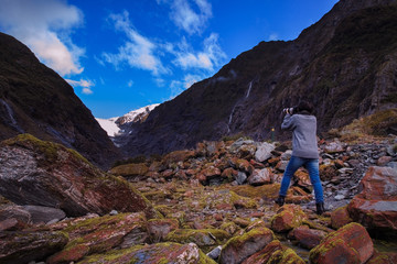 younger female photographer take a photograph in franz josef gla
