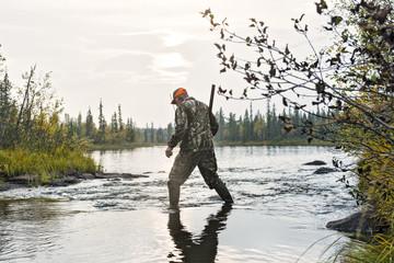 Hunter crossing river
