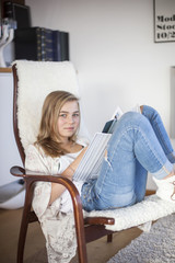 Blond girl sitting on chair and reading