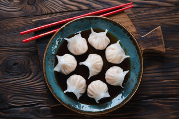 Glass plate with dim-sums in soy sauce, rustic wooden setting
