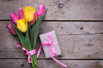 Bright yellow and pink spring tulips and box with present on vin