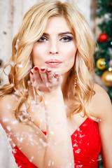 Portrait of beautiful blonde young woman in gorgeous red dress and evening make-up and hair style over christmas background