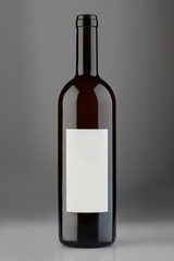 Opened red wine bottle with blank label on gray background, clipping path
