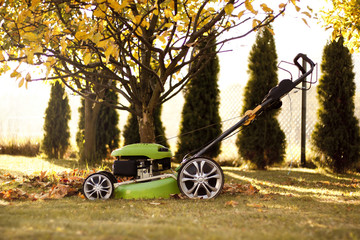 Green lawn mower in the garden at sunset