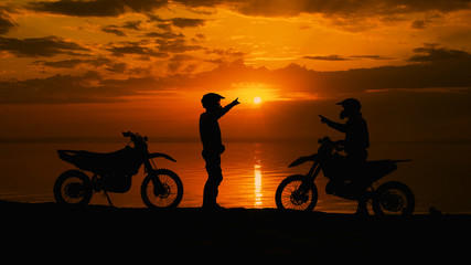 Two motorcyclists at sunset communicate. They are naberegu River, near his motocross bike.