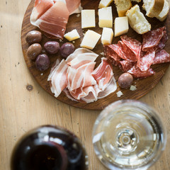 Traditional italian apero: white wine and plate with  prosciutto crudo, salami, parmesan cheese, olives and bread