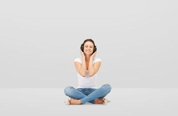 smiling young woman or teen girl in headphones