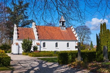 Classic white danish brick chapel with red clay layered roof tiles and a small bell tower