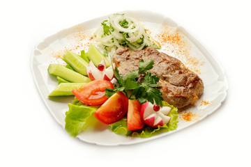 Steak with vegetables on a white background