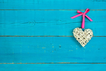Wicker heart with pink ribbon hanging on teal blue background