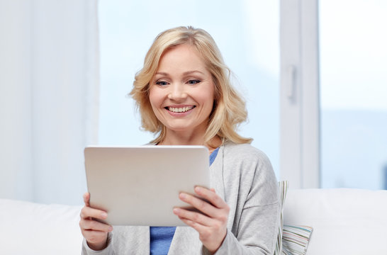 happy middle aged woman with tablet pc at home