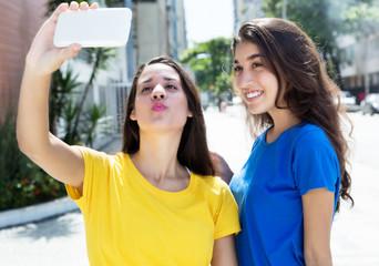 Zwei Freundinnen in bunten Shirts machen Fotos