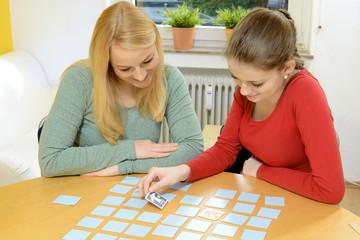 Frau mit Freundin spielt Gesellschaftsspiel