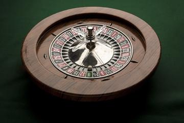 Visione laterale dall'alto di Roulette in legno intera su tavolo verde con pallina bianca