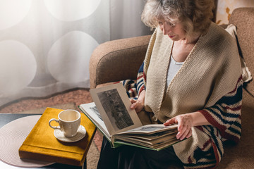 an elderly woman looks at photo albums