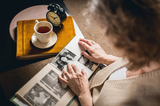 an elderly woman looks at your picture in the album made many years ago