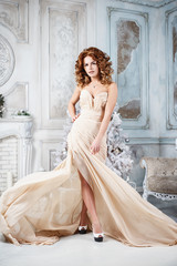 Beautiful brunette young woman in luxurious long dress in expensive interior