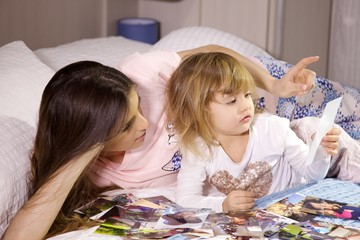 Happy mother in bed with daughter looking pictures of family