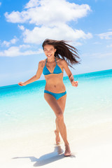 Beach sexy bikini Asian woman having fun coming out of water running laughing playful relaxing on tropical getaway paradise. Young ethnic model with slim weight loss beach body. Summer vacation travel