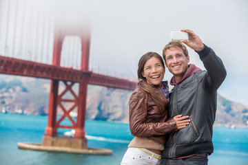 Wall Mural - Couple tourists taking selfie photo in San Francisco by Golden Gate Bridge. Interracial young modern couple using smart phone by famous american landmark. Asian woman, Caucasian man.