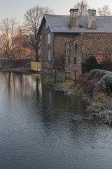 Sunrise landscape with riverbank and brick old house