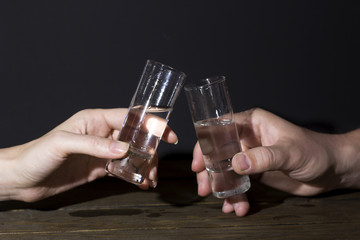 Two glasses of vodka in the hands of women and men
