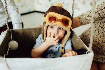 Happy kid playing and picking his nose in handmade basket of air balloon. Child having fun at home with parents. Young pilot indoors. Boy in hat like a helmet looking left.