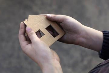 homeless boy holding a cardboard house