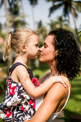 mother and preteen daughter summer portrait in the green beautiful park