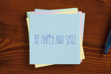 Be happy and smile handwritten on note