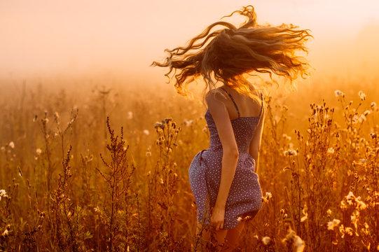 Dancing beautiful girl in fog, field, sun backlight, sunrise, orange colors