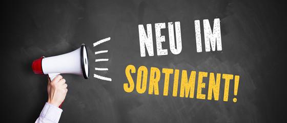 "Megafon vor Kreidetafel mit Slogan ""Neu im Sortiment"""