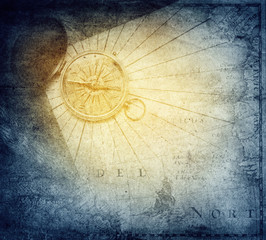 Vintage golden compass with nautical map background.