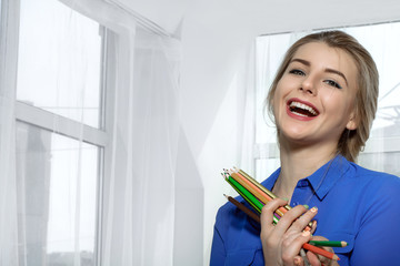 Girl laughs holding pencils in hands.