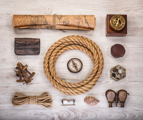 Fototapete - Overhead view of pirate or sailor gear laid out for a backpacking trip on a old wood floor. Items include, rope, compass, money, map, binoculars, sextant , shell. Stories background.