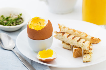 Soft boiled egg with toast for rich breakfast.