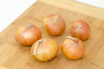 Food and picnic topic: onion lying on a wooden board in the background of green grass