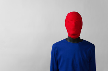 Surrealism Theme: man in a blue jacket with a red cloth tied around his head is in the corner on a gray background
