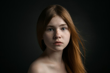 Dramatic portrait of a girl theme: portrait of a beautiful girl on a background in the studio