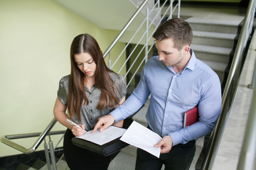 Portrait of a smiling young business couple standing with arms crossed in a office