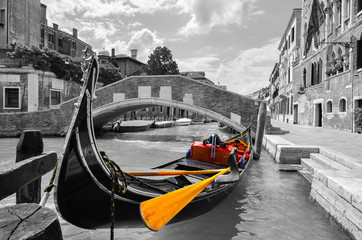 Black and white of a beautiful canal in Venice with selective color on the gondola