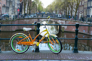 Orange  bicycle next to canal of Amsterdam