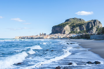 Empty beach of Cefalu leading to its old town in a sunny winter day. Sicily. Italy