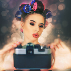 cute girl make a foto selfie at vintage camera.