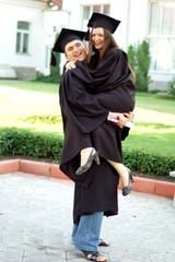 A graduates in the mantle embrace and enjoy. Beautiful graduate girl and boy enjoyed the ceremony graduation.